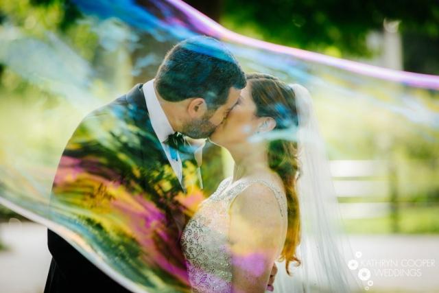 Couple kisses in bubble - unique wedding photos by creative wedding photographer Kathryn Cooper Weddings