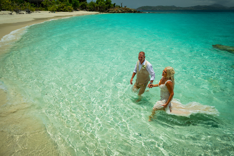 Couple gets married and jumps in beach water with wedding clothes on