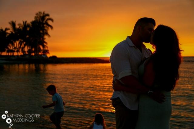 Couple kisses during Waikaloa beach sunset photos Hawaii Big Island